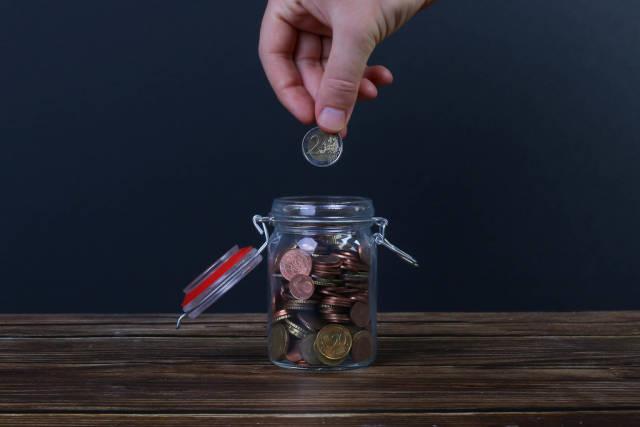 Hand putting coin in money jar