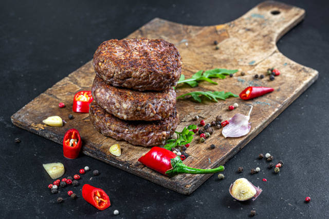 Fresh meat cutlets with spices, pieces of chili and garlic on an old kitchen Board