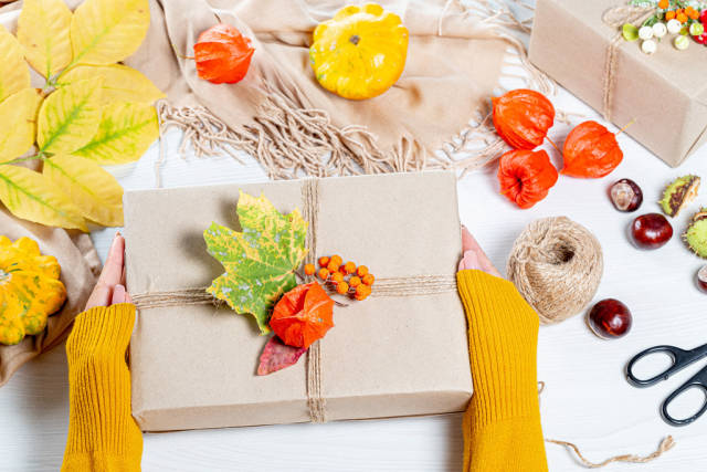 Beautifully packaged gift in autumn style in womens hands. Family holiday concept, Thanksgiving Day