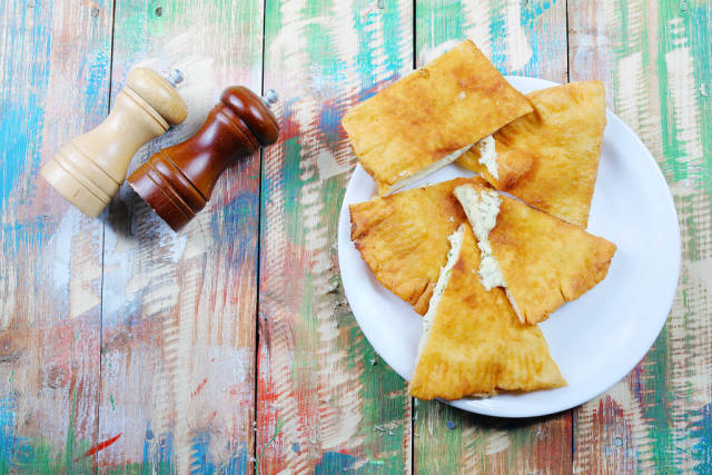 Hungarian Langos with cheese, salt and pepper on a colored vintage wooden background