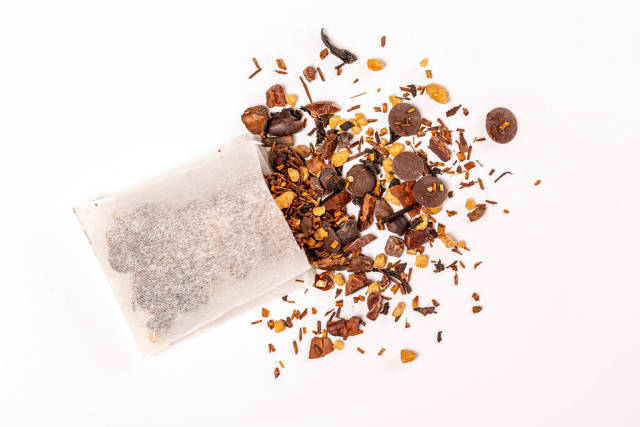 Top view, tea bag with scattered black tea with chocolate and pieces of nuts