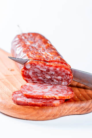 Delicious sliced sausages on table