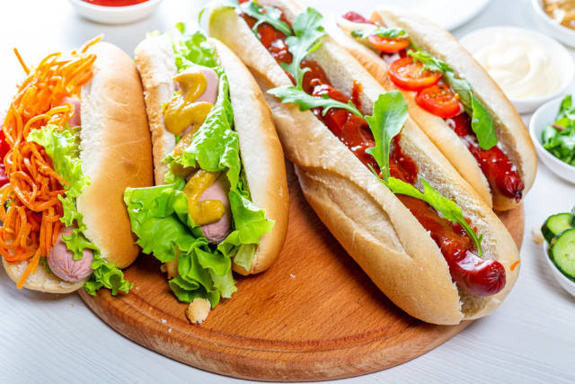 Hot dogs fully loaded with assorted toppings on a tray. Food background