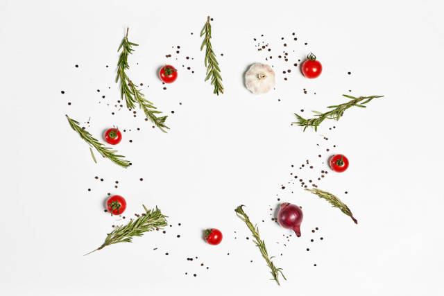 Composition of fresh cherry tomatoes, onion and garlic with herbs on white background