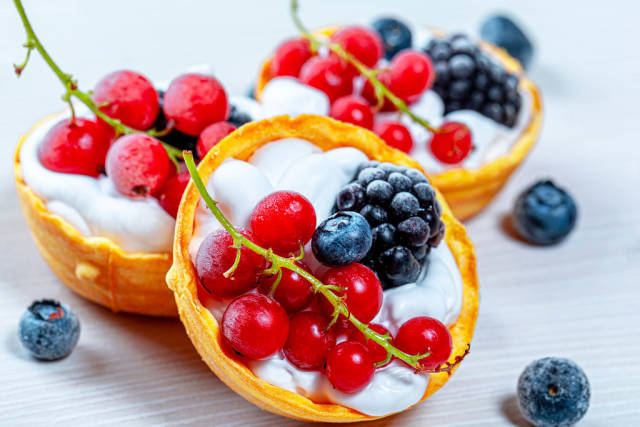 Close-up of tartlets with white cream, red currant, mulberry and blueberry