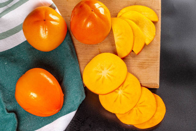 Ripe persimmon slices and whole fruit