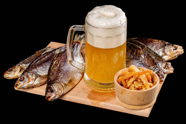 Glass of beer with dried fish on a dark background