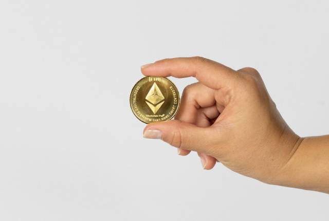 Woman holding a physical Ethereum coin