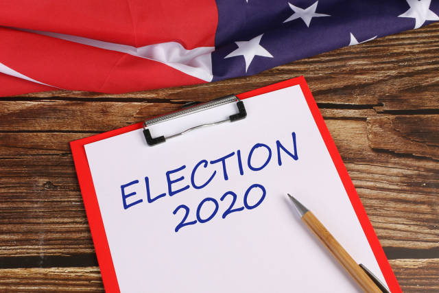 American flag on wooden table with Election 2020 text
