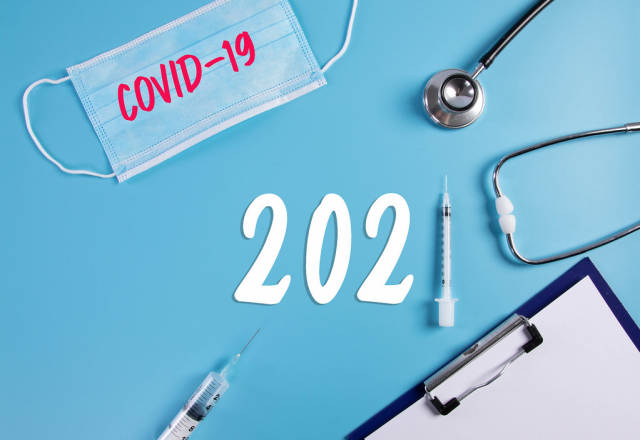 Medical face mask, clipboard, stethoscope and syringe with 2021 text on blue background