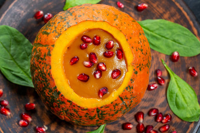 Pumpkin puree with fresh pomegranate seeds and spinach. The view from the top