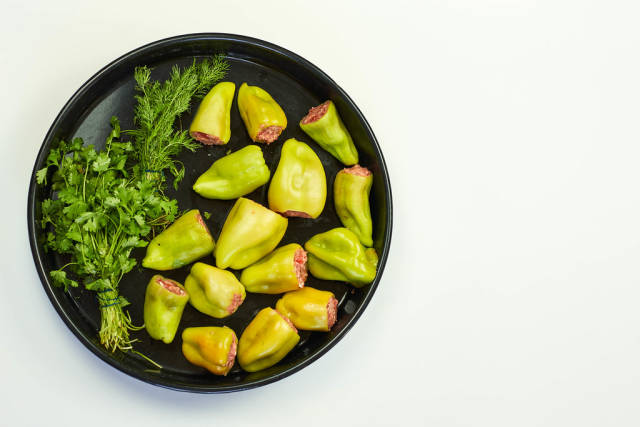 Top view of green bell papers with parsley on white