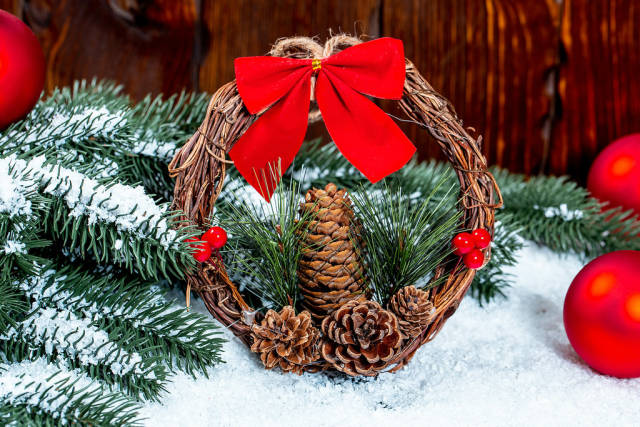 Wreath with a red bow, cones and branches on a snow background. The concept of the traditional symbol of the Christmas holidays