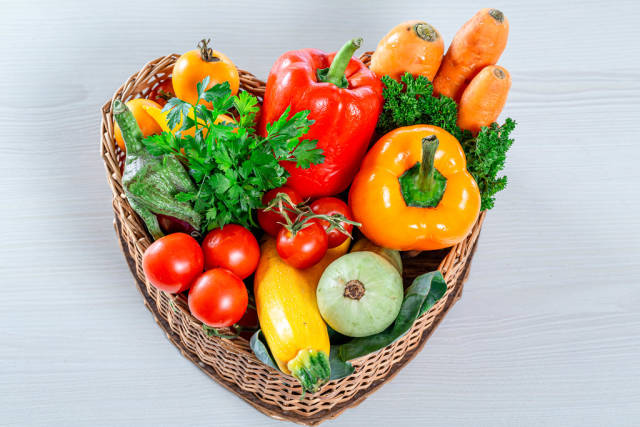 Wicker basket in the shape of a heart filled with fresh vegetables and herbs