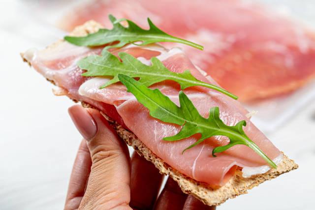 Diet sandwich with crispbread, dry-cured ham and arugula in women hand