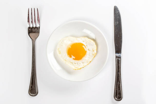 Top view, fried egg heart on a white plate