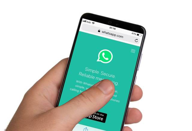 Male hands holding smartphone with an open Whatsapp application