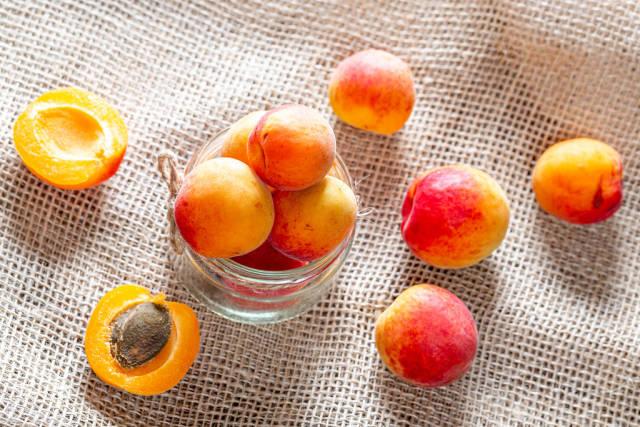 Orange ripe apricots on burlap background