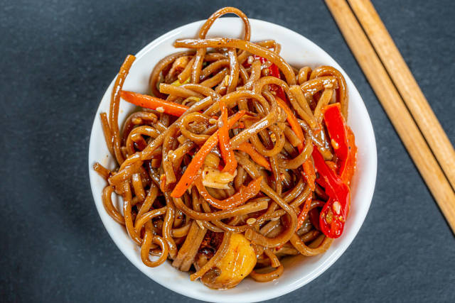 Thin buckwheat noodles with sauce, vegetables, mushrooms and sesame in bowl on black background with chopsticks