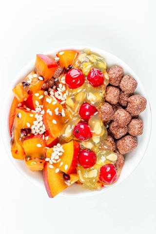 Top view, corn balls with slices of tamarillo, kiwano and red currant on a white background