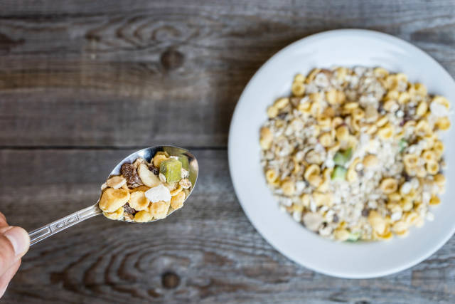 Close Up On The Hand Holding The Spoon With Muesli