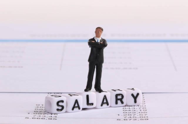 Businessman figure standing on Salary text