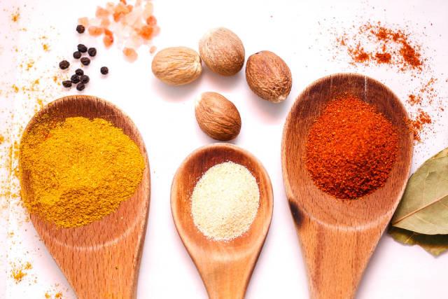 Chili, Curry und Knoblauchpulver Gewürze in Holzlöffeln vor weißem Hintergrund