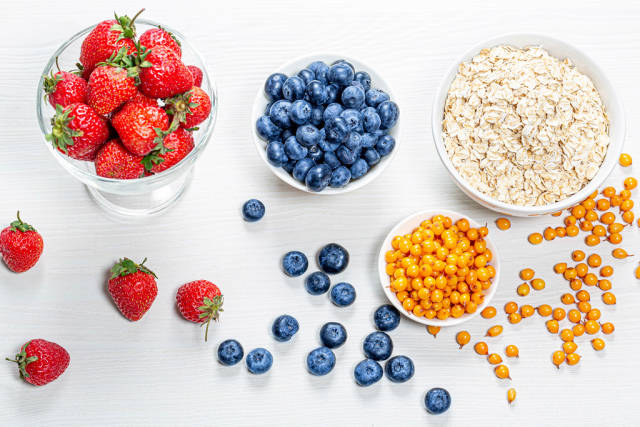 Raw oatmeal with fresh berries and almonds on a white wooden background
