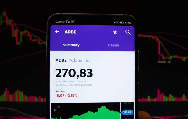 A smartphone displays the Adobe Inc. market value