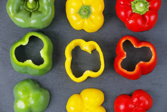 Fresh green, red and yellow pepper, black background