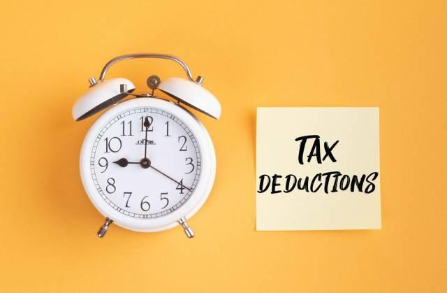 Wecker und ein Zettel mit 'Tax deductions' Text vor gelbem Hintergrund