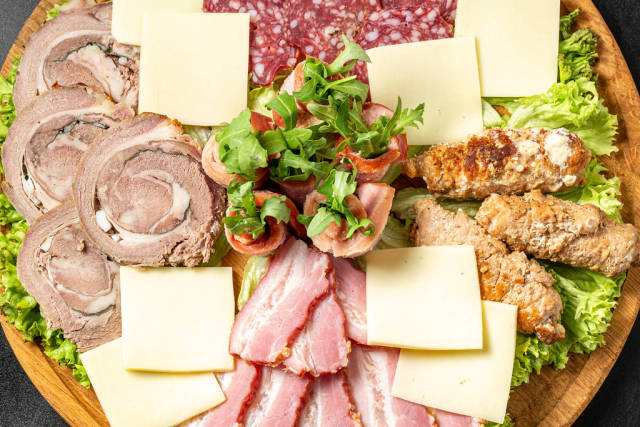 Wooden board with meat, salami and cheese cuts