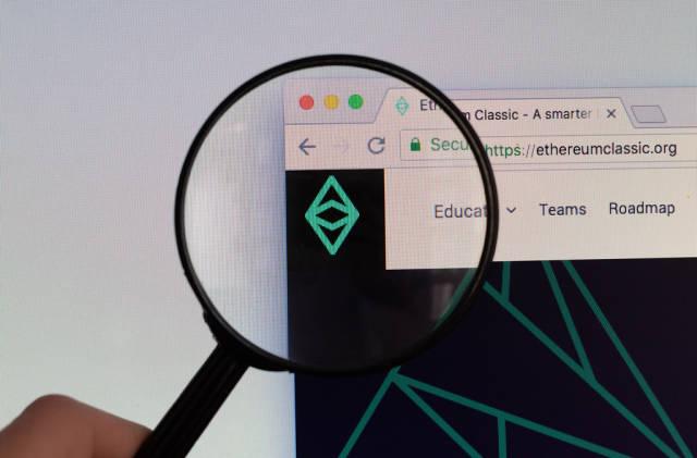 Ethereum Classic Logo am PC-Monitor, durch eine Lupe fotografiert