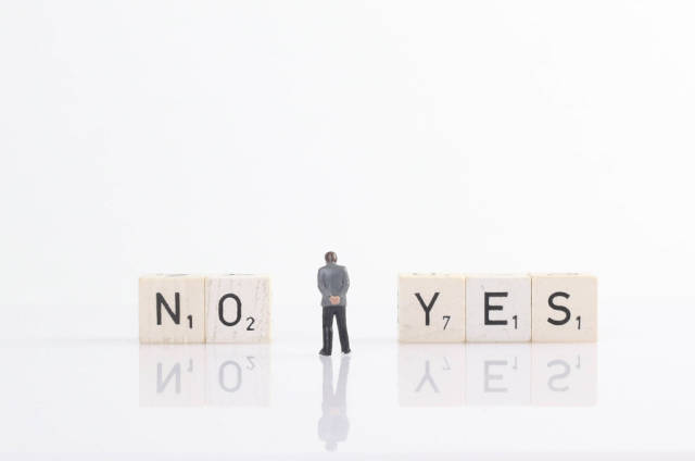 Businessman standing next to yes and no text on wooden blocks