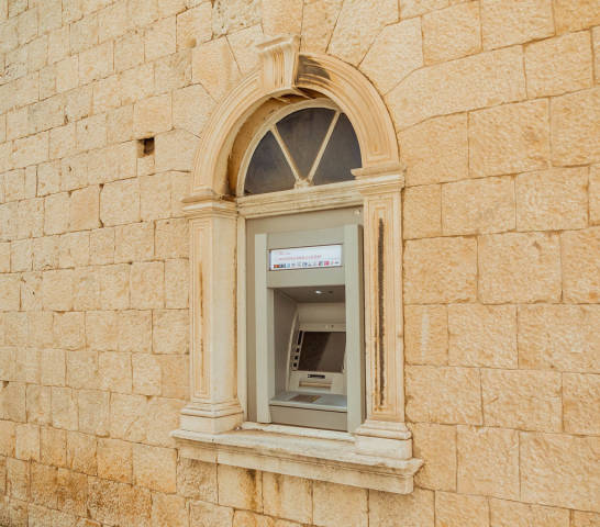 Old outdoor ATM machine on wall