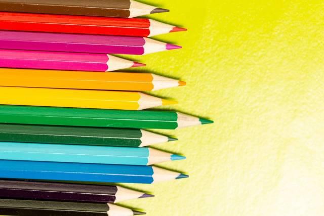 Nach Farben sortierte Buntstifte auf gelbem Untergrund