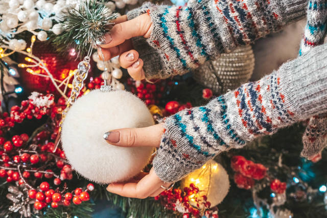 Close-up, female hands with a white ball decorate the christmas tree