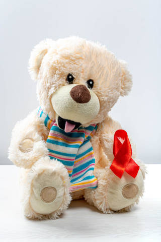 Childrens toy bear with red ribbon as a symbol of the fight against childrens cancer