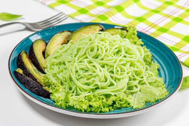 Vegetarian lunch-green spaghetti with avocado and lettuce