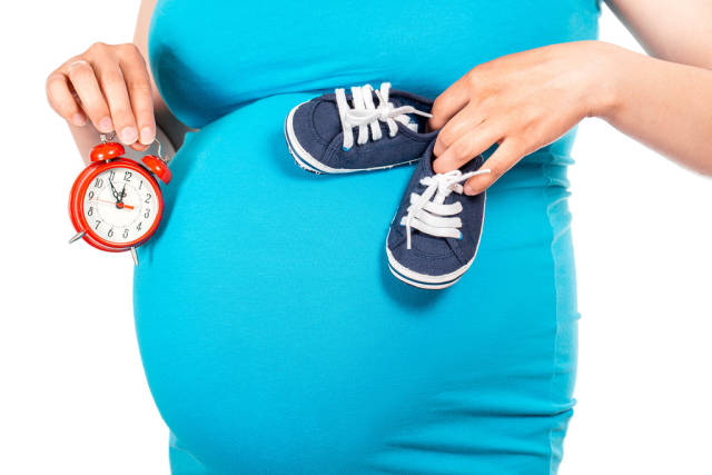 Beautiful small blue shoes at the pregnant womans belly and red alarm in hand