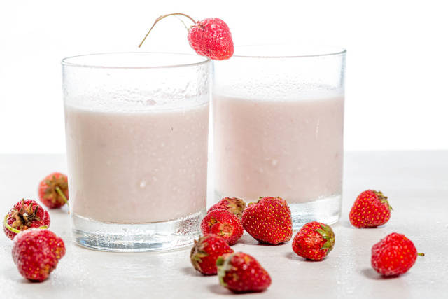 Two glasses of yogurt and fresh red strawberries