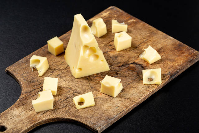 Slices of fresh Maasdam cheese on an old wooden kitchen board