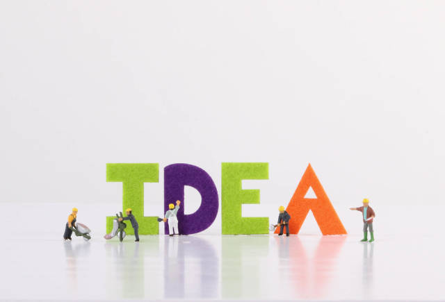 Miniature workers with Idea text on white background