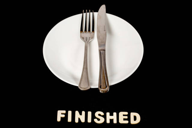 Fork and knife on a empty plate, dining etiquette concept, finishing meal