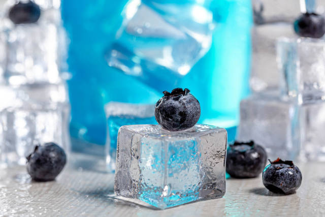 Close-up of blueberries on ice cube with blue cocktail behind