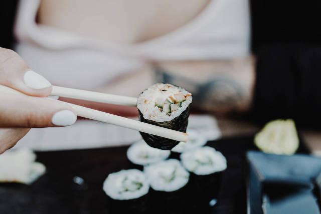 Junge Frau isst Sushi mit Essstäbchen