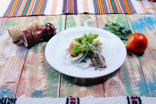 Pork steak with tomatoe, salt and pepper, wooden background
