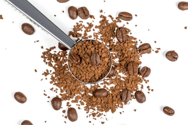 Instant coffee and whole coffee beans on a white background with an iron spoon