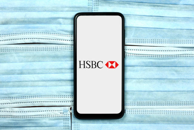 HSBC Investment banking company logo on smartphone screen over the face masks