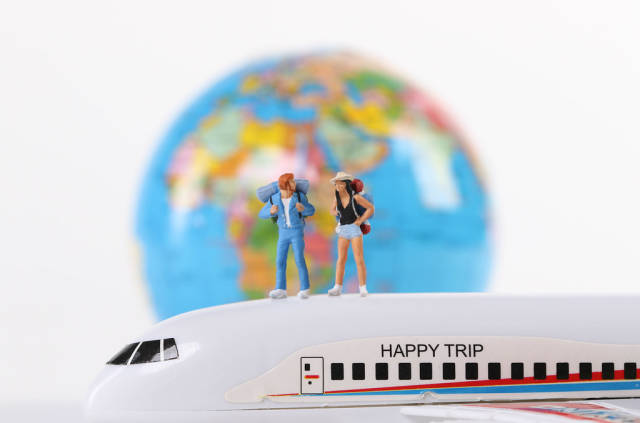 Miniature travelers standing on airplane with globe in the background